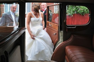 bride getting in vintage wedding car