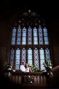 matfen hall wedding bride and groom on stairs infront of stained glass window