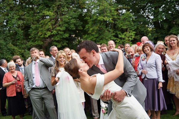 groom kissing bride at ellingham hall wedding