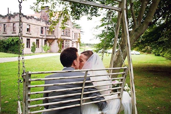 bride and groom kissing on swing at ellingham hall wedding