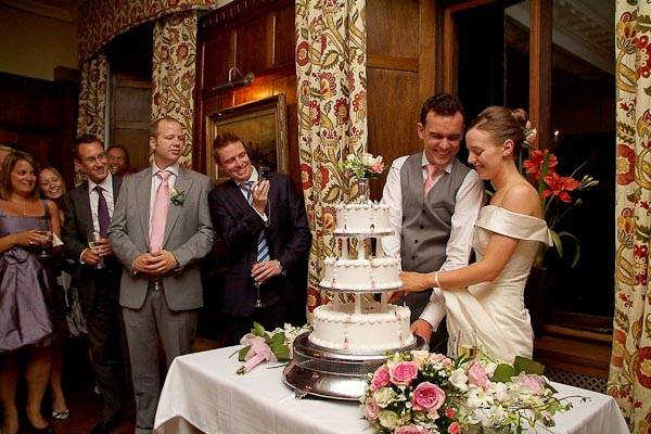 cutting the cake at ellingham hall wedding
