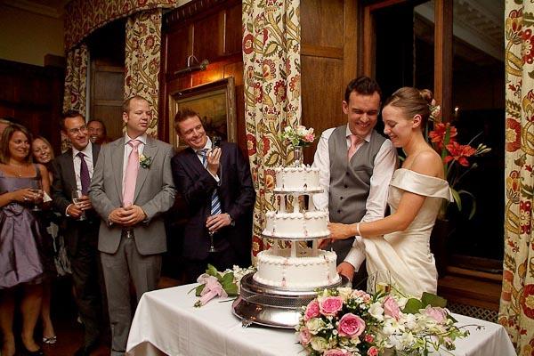 cutting the cake at ellingham hall wedding