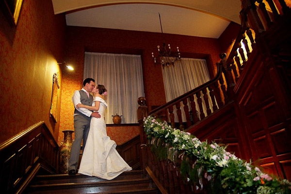 bride and groom kissing on stairs at ellingham hall wedding