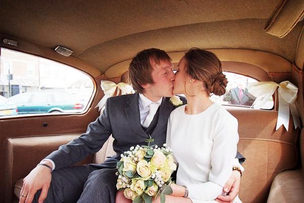 bride and groom kissing in vintage wedding car