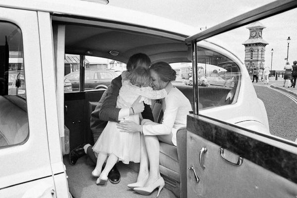 bride groom and flowergirl in wedding car