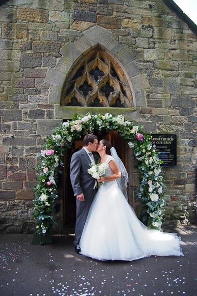 bride and groom kissing outside church of our lady at seaton delaval hall wedding