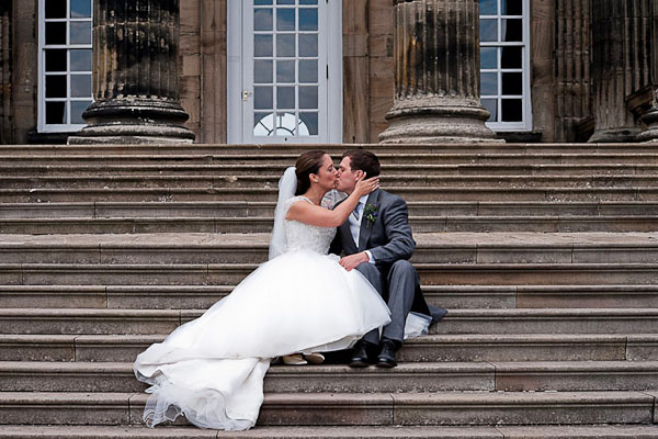 bride and groom kiss on stairs at seaton delaval hall