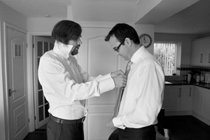 groom and best man getting ties on