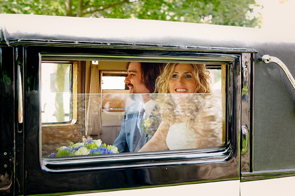 bride and groom in classic wedding car