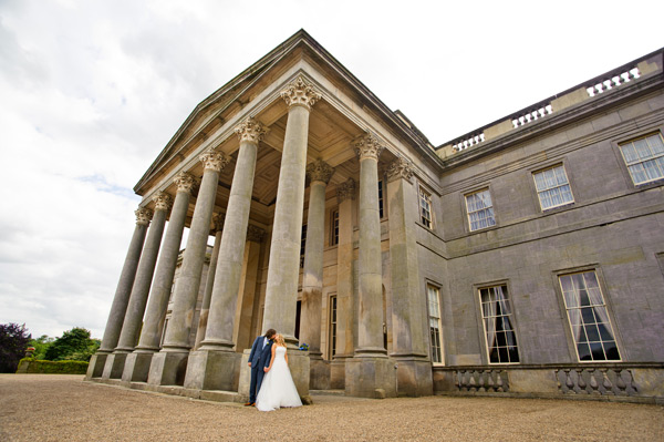 Wynyard Hall Wedding Photographer bride and groom kiss next to pillars