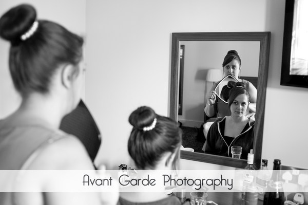 bridesmaid checking back of hair in mirror