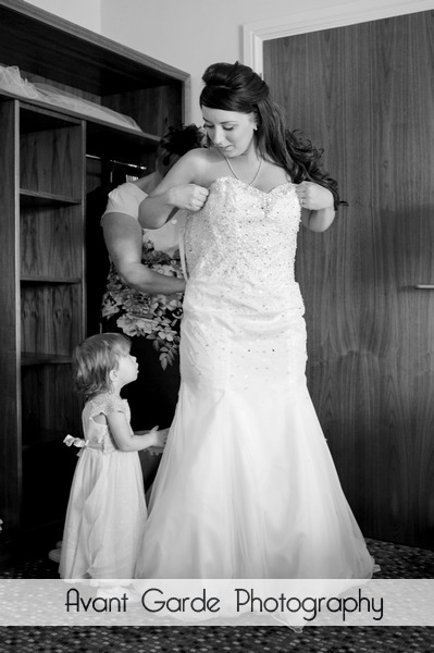 Mother of bride helping daughter get into wedding dress with grand daughter watching