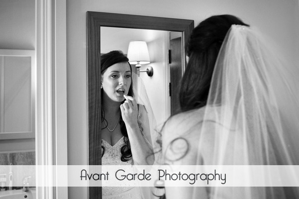 bride putting on lipstick in mirror