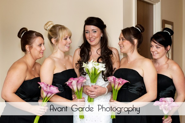 bride and bridesmaids in black dresses holding bouquets in hotel room before wedding at Alnwick Castle