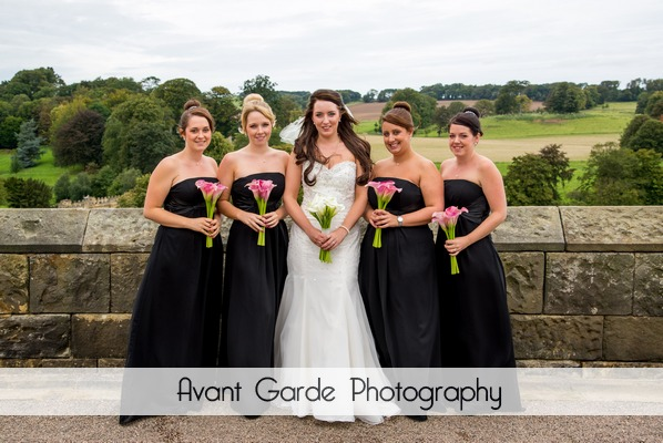 bride and bridesmaids with bouquets in grounds of Alwick Castle