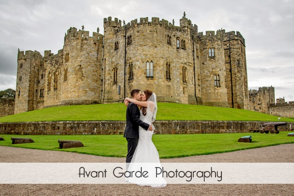 bride and groom kiss in front of Alnwick Castle