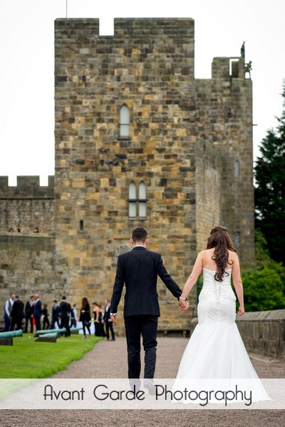 bride and groom walking in grounds of castle