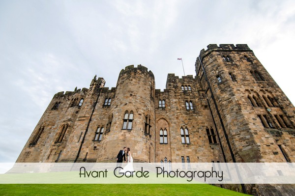bride and groom with Alnwick castle in background