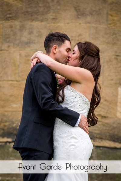 bride and groom kiss in grounds of alnwick castle