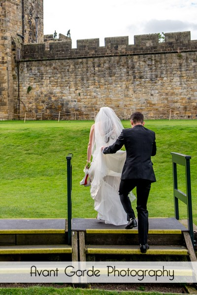 groom holding back of wedding dress as bride walks up steps