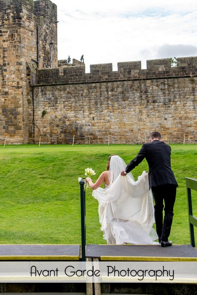 bride and groom waling in castle grounds