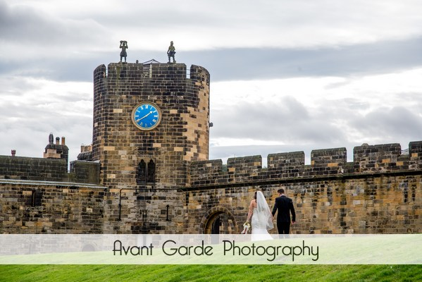 bride and groom walking at Alnwick castle