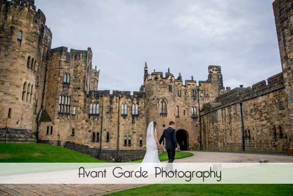photo of alnwick castle wedding with bride and groom walking
