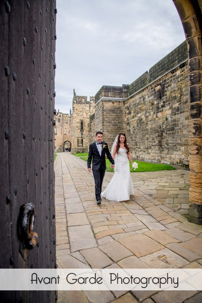bride and groom walking though castle door
