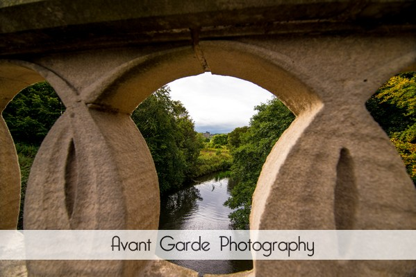 view of Alnwick castle and river taken through bridge