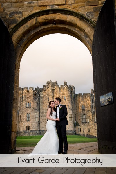 groom kissing brides temple in castle archway