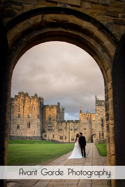 view through archway of couple kissing with alnwick castle in background