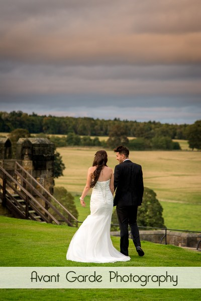 back of bride and groom in alnwick castle grounds