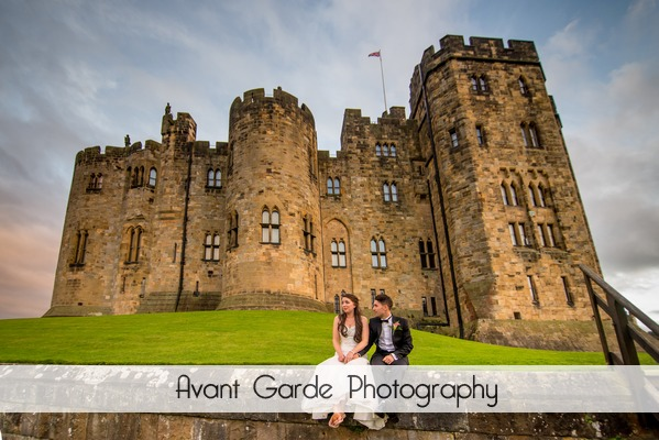 bride and groom sat on wall with alnwick castle behind them and amazing sky