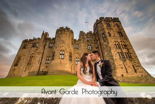 bride and groom kissing sat on castle wall with view of alnwick castle behind them