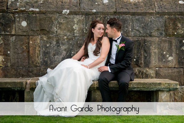 bride and groom on stone bench